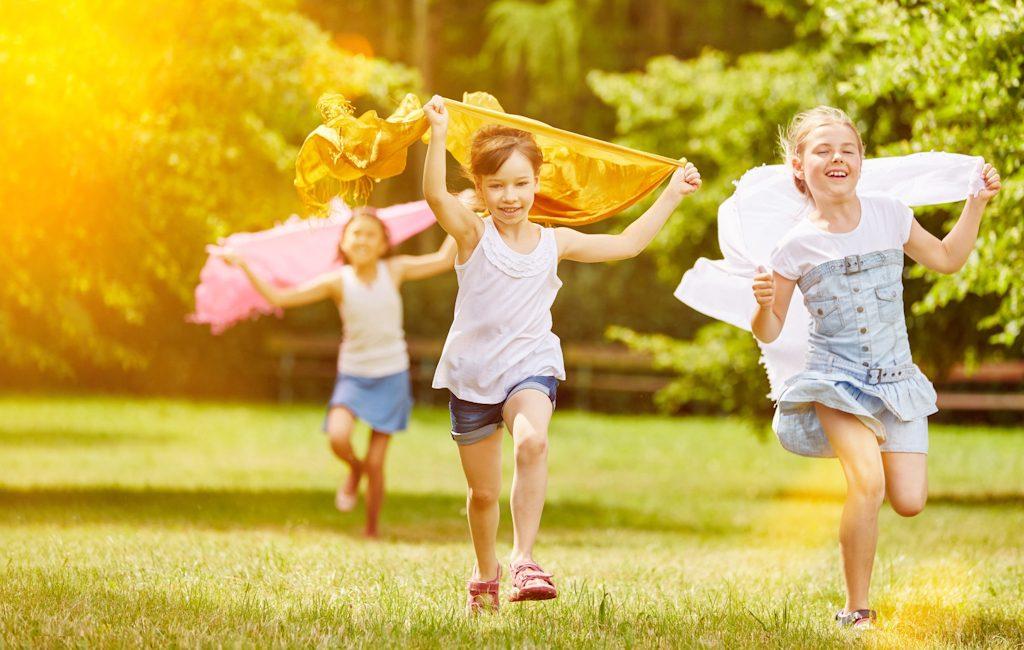 Fröhliche Mädchen laufen und haben Spaß im Sommer mit Tüchern